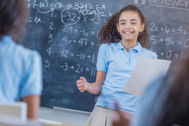an girl standing in front of a chalkboard full of equations and smiling