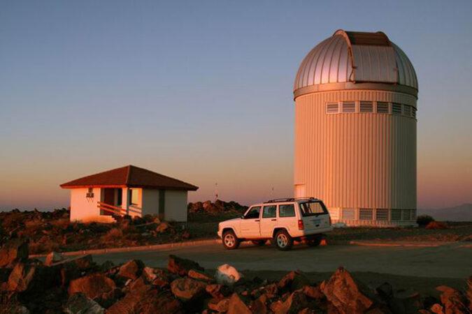 a phot of the OGLE telescope against an orange sky