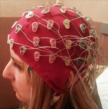 a woman wearing an EEG cap covered in sensors