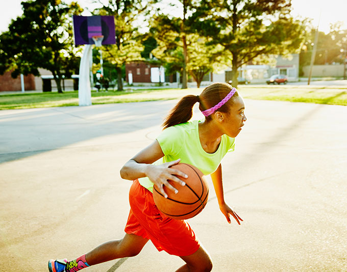 a girtl dribbling a basketball on an outside court