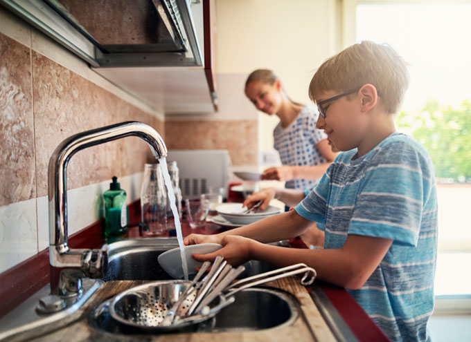 a boy and a girl doing dishes