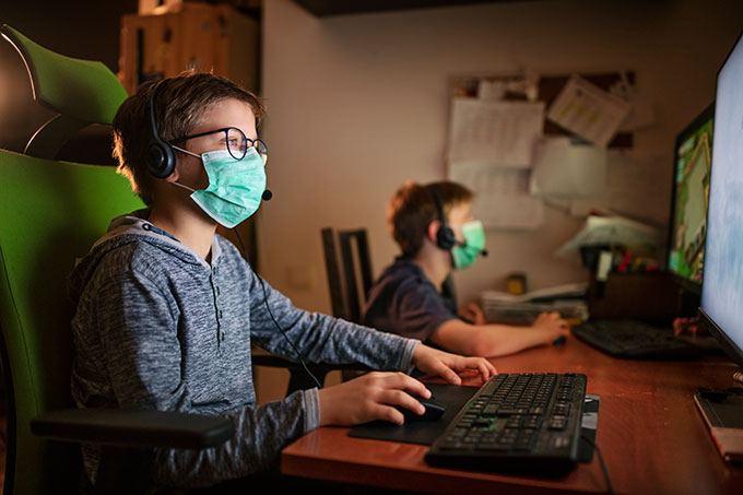 two boys wearing face masks and playing computer games
