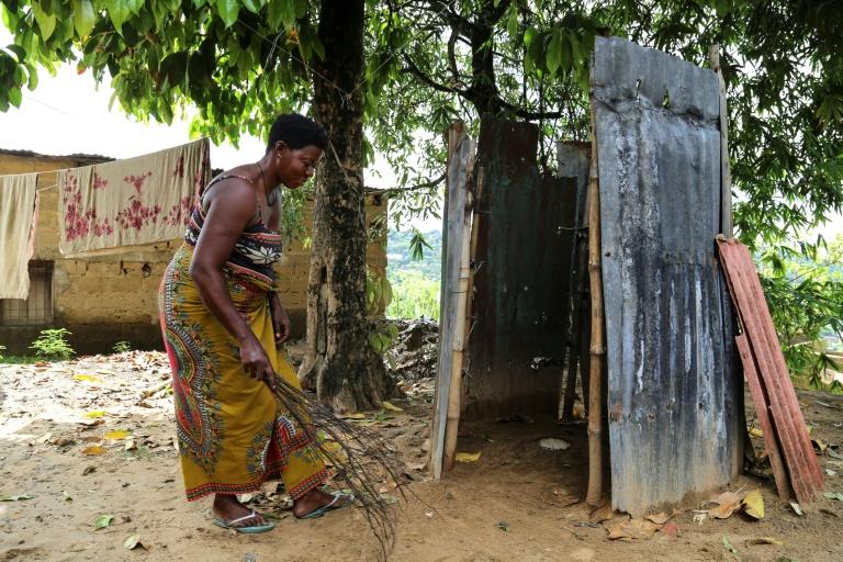 Nettoyage de toilettes rudimentaires dans un quartier populaire de Kinshasa le 17 novembre-AFP/SAMIR TOUNSI