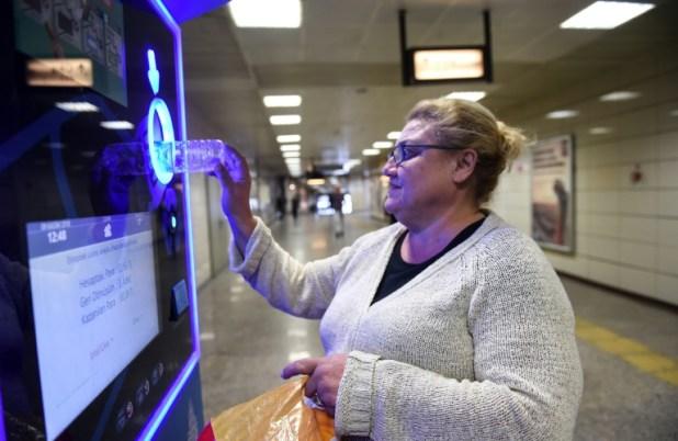 Tülay Gerçek insère des bouteilles en plastique dans une machine de recyclage qui crédite sa carte de transport, le 9 novembre 2018 dans le métro d'Istanbul (AFP - BULENT KILIC)