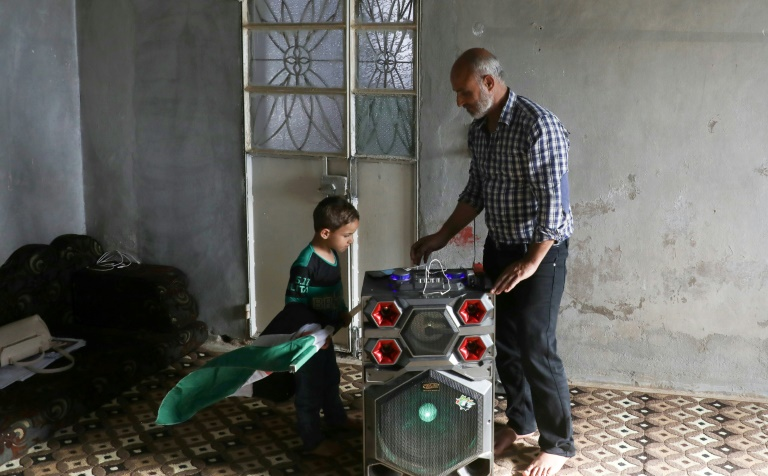 Zakariya Sinno and her son turn on a solar-powered sound system installed on their roof, in the village of Killi, in Idleb in northwestern Syria, on June 9, 2021. (AFP - Aaref WATAD)