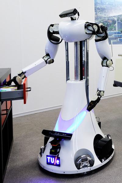 AMIGO staat voor Autonomous Mate for IntelliGent Operations. De robot is ongeveer anderhalve meter hoog. De robot is uitgerust met meerdere camera's, zodat deze diepte kan 'zien'. Ook beschikt de robot over Laser Range Finders (LRFs) waarmee deze in 3D een beeld van zijn omgeving krijgt. Foto: TU Eindhoven.