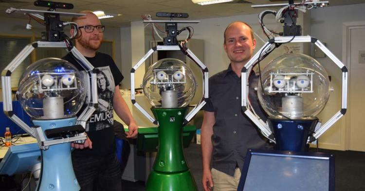 Twee onderzoekers (links Nick Hawes) met drie robots die binnen het STRANDS-project zijn ontwikkeld. Bob staat in het midden. Afbeelding: University of Lincoln.