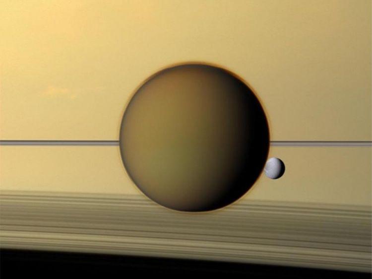 Een fraaie compositie van de manen Titan en Dione voor Saturnus. Op deze foto is de atmosfeer van Titan duidelijk te zien, terwijl Dione scherp afsteekt tegen de achtergrond.