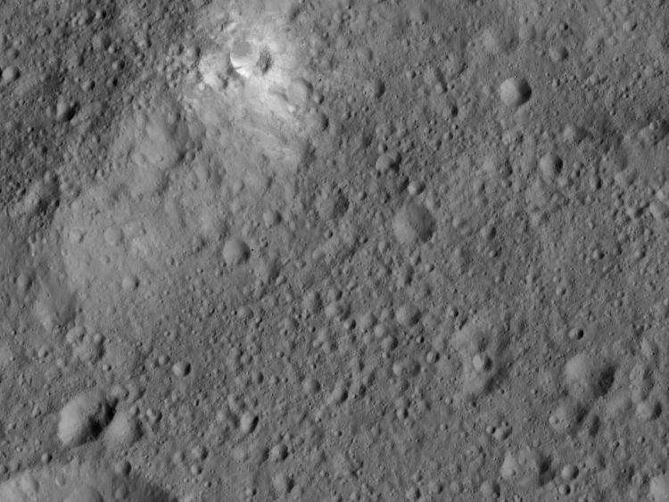 Toen Dawn Ceres naderde, zag de sonde vreemde, heldere vlekken op het oppervlak van de dwergplaneet. Inmiddels zijn ons 130 plekken op het oppervlak van Ceres bekend waar deze heldere vlekken acte de présence geven. Hier zie je zo'n plek (linksboven). Tevens weten we ondertussen hoe de heldere vlekken zijn ontstaan: zout water op het oppervlak is gesublimeerd en liet zouten achter. En die zouten reflecteren meer zonlicht. Afbeelding: NASA / JPL-Caltech / UCLA / MPS / DLR / IDA.