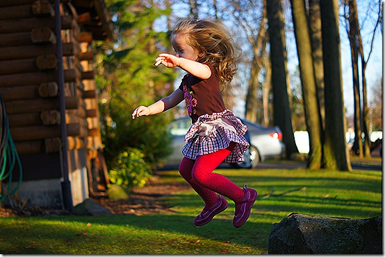 My two-year-old jumping off a rock by her uncle's Pennsylvania log cabin