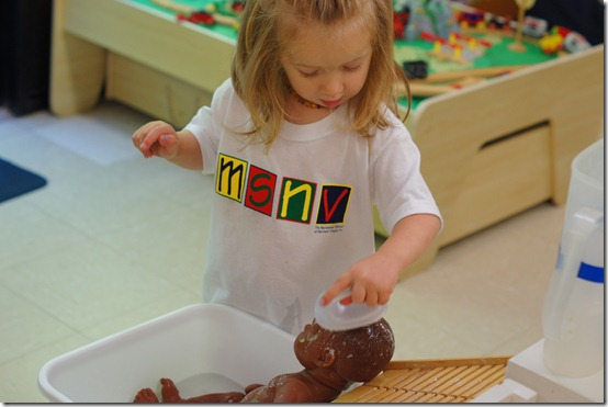 Showing her brother how to wash a baby with soap - at the Montessori School of Northern Virginia