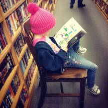 A small girl reading in a bookstore - help kids love to read