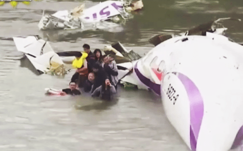 Shocked survivors climb out of the wreckage of the plane after it crashed in Taiwan's Keelung River. Photo: Screengrab