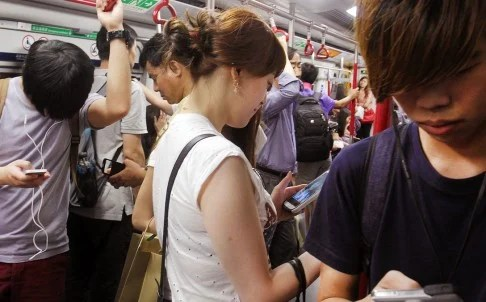 The MTR Corp worries that passengers checking their phones are not paying adequate attention to safety concerns. Photo: Dickson Lee