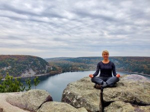 Woman with spinal fusion and scoliosis sitting on mountain top meditating and practicing pranayama