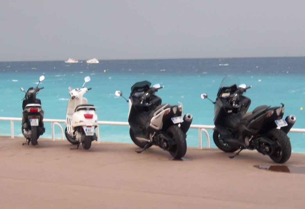 Scooters sunning themselves at the water's edge, along the Promenade des Anglais in Nice