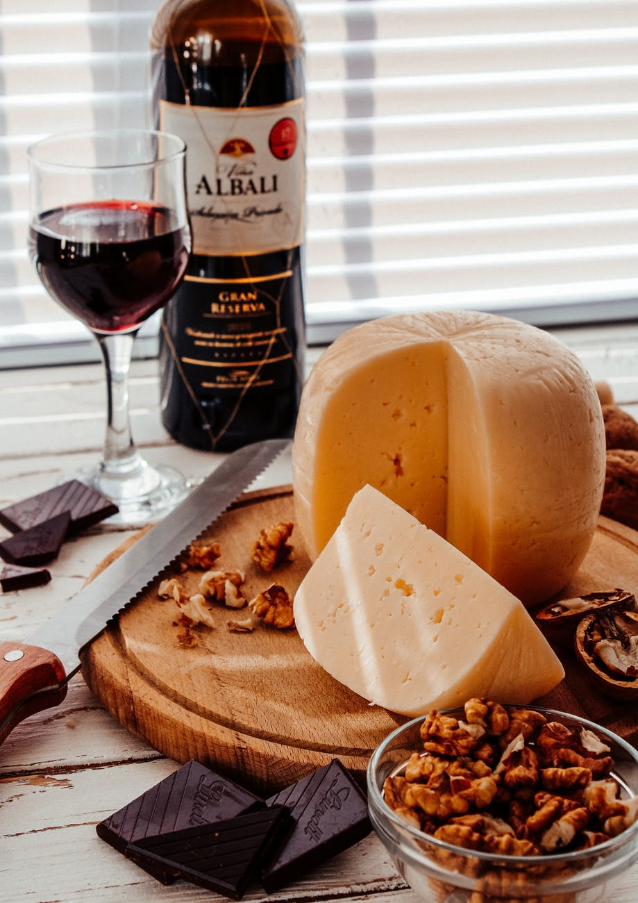 cheese and wine on brown wooden chopping board