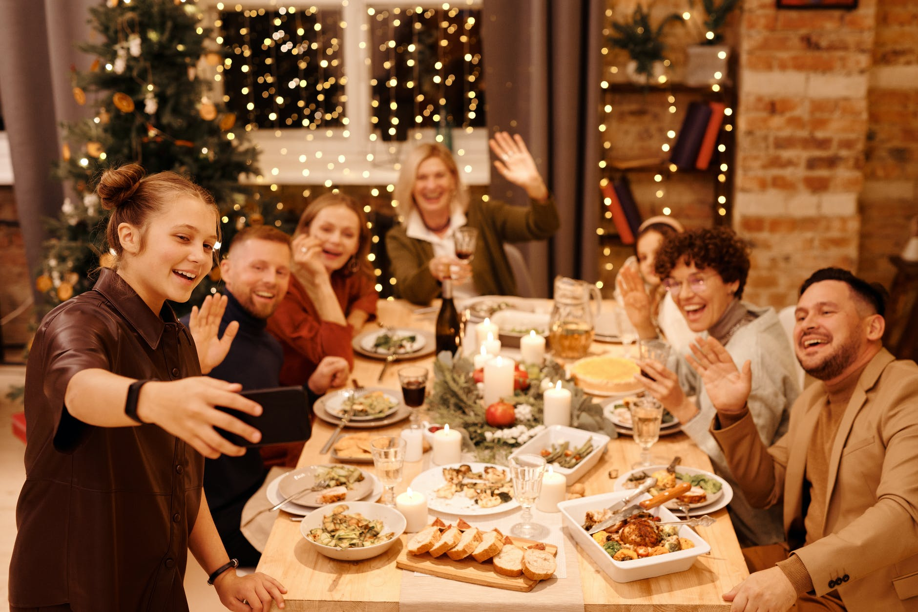 family celebrating christmas dinner while taking selfie