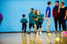 Athletics session with girl carrying relay baton and team behind her
