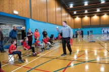 Graham Harvey from FVDS coaching boccia to players lined up in seats at edge of court