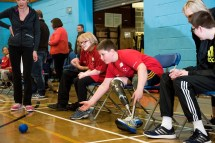 Double leg amputee seated and throwing boccia ball with other participants lined up beside