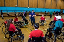 Wheelchair basketball players in a circle around coach Jen Scally