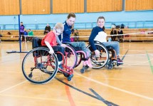 Shelby Watson demonstrating wheelchair skills to two other wheelchair users alongside