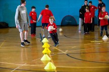 Young ambulant athlete taking part in football drill