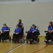Four participants using wheelchairs lined up to try boccia throws