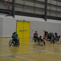 Wheelchair basketball game in progress with coach