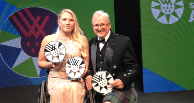 Sammi and Richard on stage with their awards
