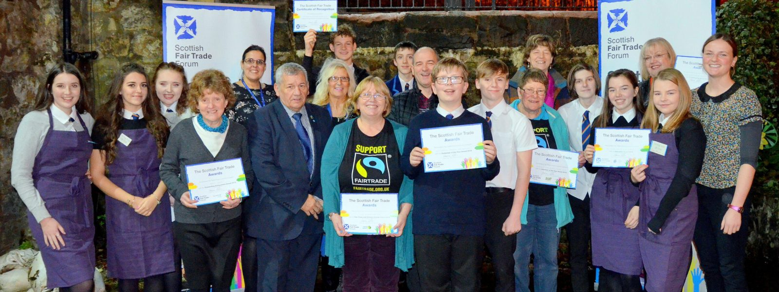 Group of children and few adults showing their Scottish fair Trade Award