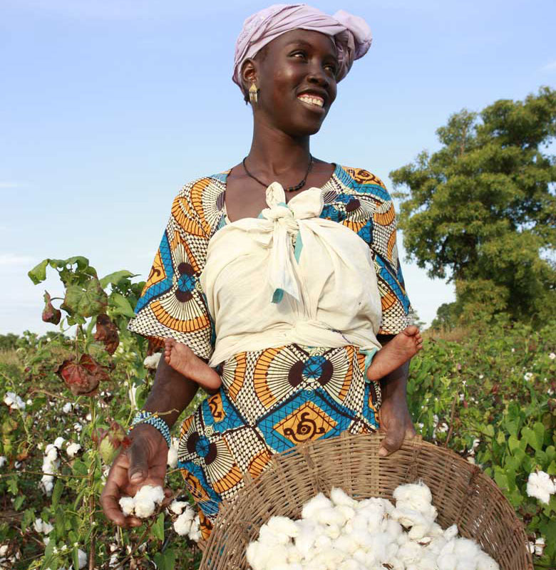 Woman who carry a child smiles while showing a basket of cotton