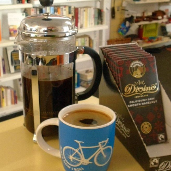 A cup of coffee lays next to some Divine chocolate bars and a pot full of coffee
