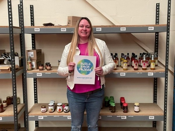 Woman holding a Build Back Fairer poster standing in front of shelves with Fair Trade products