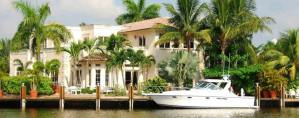 Scott Rivelli Home Slider Image of a waterfront home in South Florida with a yacht docked outside