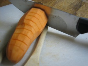 Cutting the sweet potatoes with wooden-spoon guides