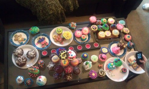 Coffee table filled with finished cupcakes and cookies, at least 60