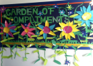 This garden of compliments bulletin board features ivy and colorful flowers