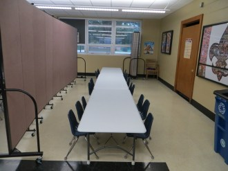 Two set of rectangular tables and chairs are divided into two classrooms with a Screenflex Room Divider
