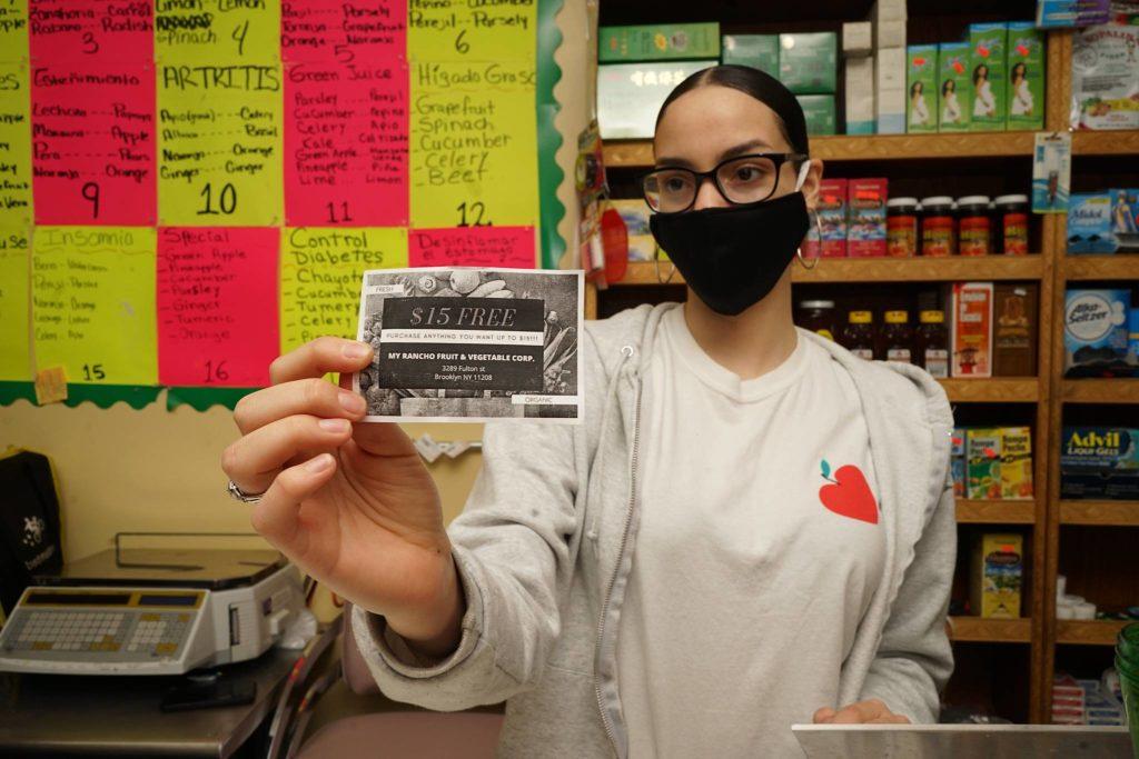 Laury Paulino, former CHCCC student, holds one of the homemade vouchers for her parents new grocery store.