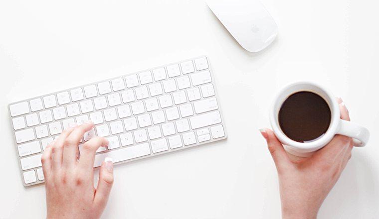 Scrivere un libro: una tastiera, due mani che digitano e una tazza di caffè.