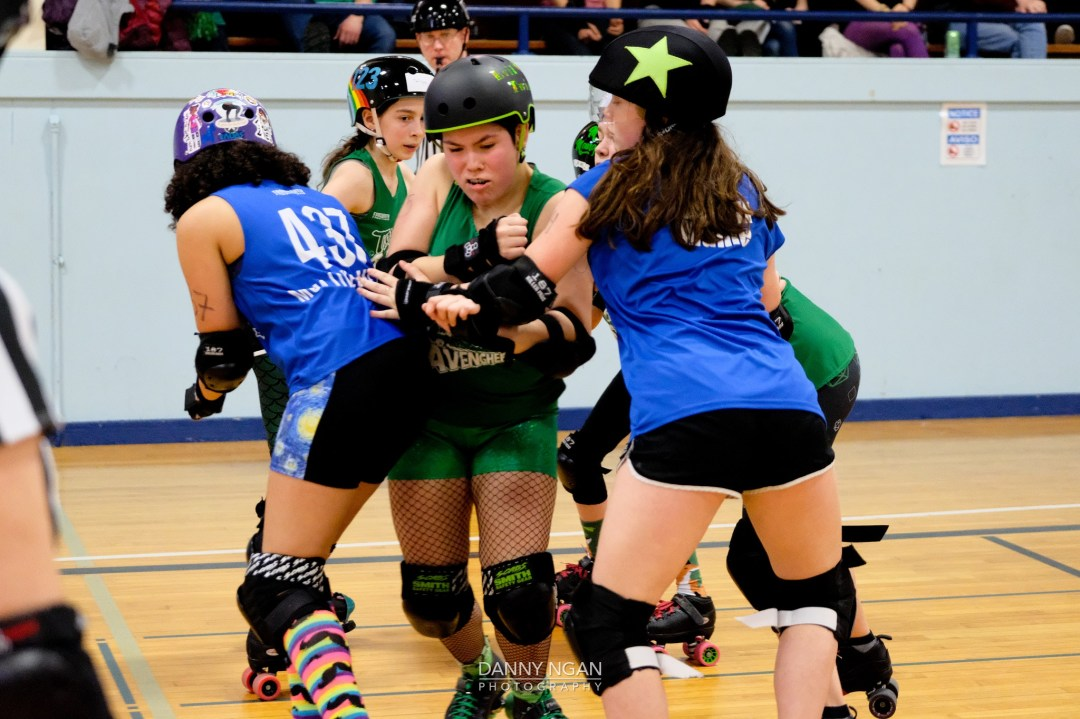 Seattle Derby Brats Toxic AvengHers skater breaking through the Mighty Rollers wall