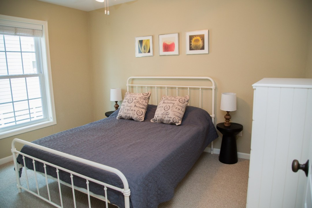 Bedroom with Beige Wall Paint, Vintage Night Stands and Three Paintings