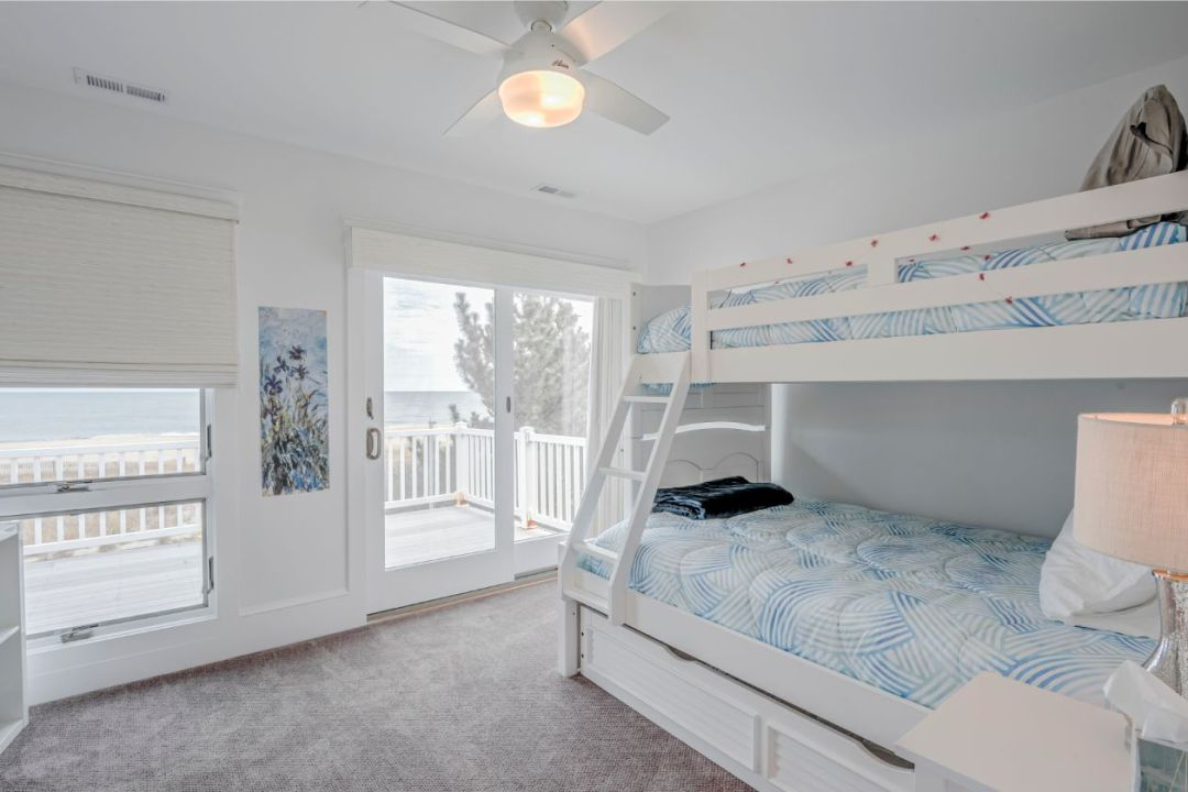 Bedroom with White Bunk Beds and White Ceiling Fan