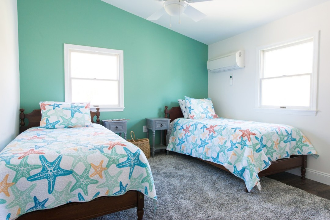 Kent Renovation Bedroom with Two Bed, Starfish Covers, Light Sea Foam and White Paint Walls, Dark Wood Flooring, Gray Carpet