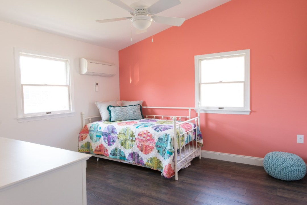 Kent Renovation Guest Bedroom with Coral and White Paint Walls, Dark Wood Flooring, Two Windows and Air Conditioner