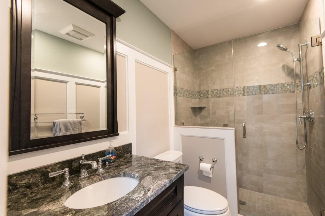 Bathroom Remodel in Kings Grant, Fenwick Island DE with Dark Wood Vanity, Nordic Grey Marble Wall Tiles and Dark Granite Top