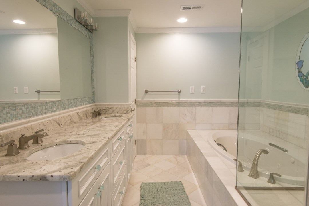 Kings Grant Renovation Vol.1 Bathroom with River Valley White Granite Top, White Vanity, Tub and Marble Tiles Floor
