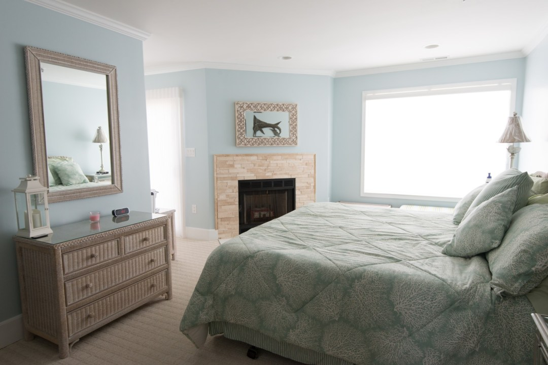 Kings Grant Renovation Vol.1 Fenwick Island, DE Bedroom with Light Blue Walls, Light Stone Fireplace, Beige Carpet and Large Window
